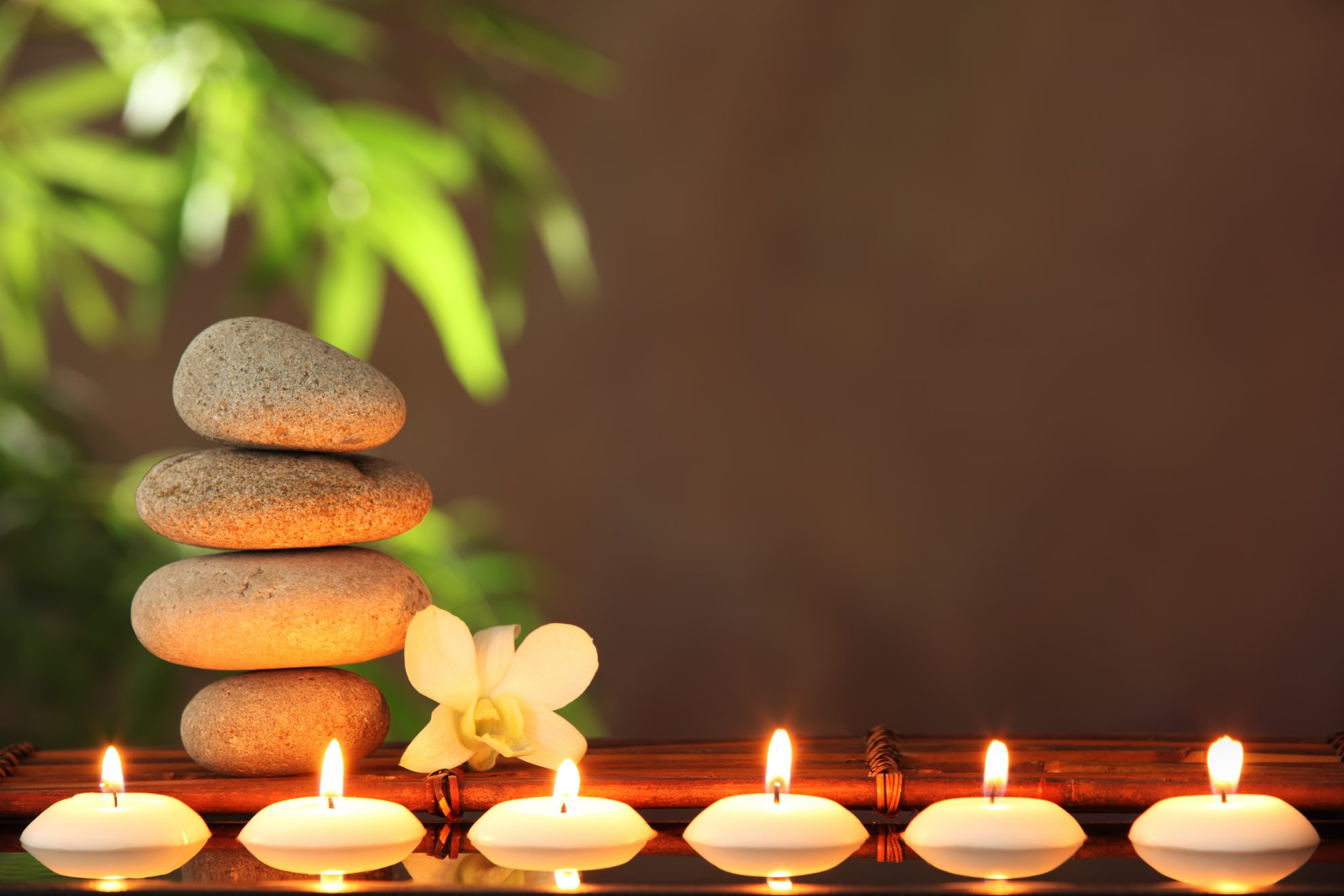 Relaxing photo of stones, candles, and orchids representing Reiki