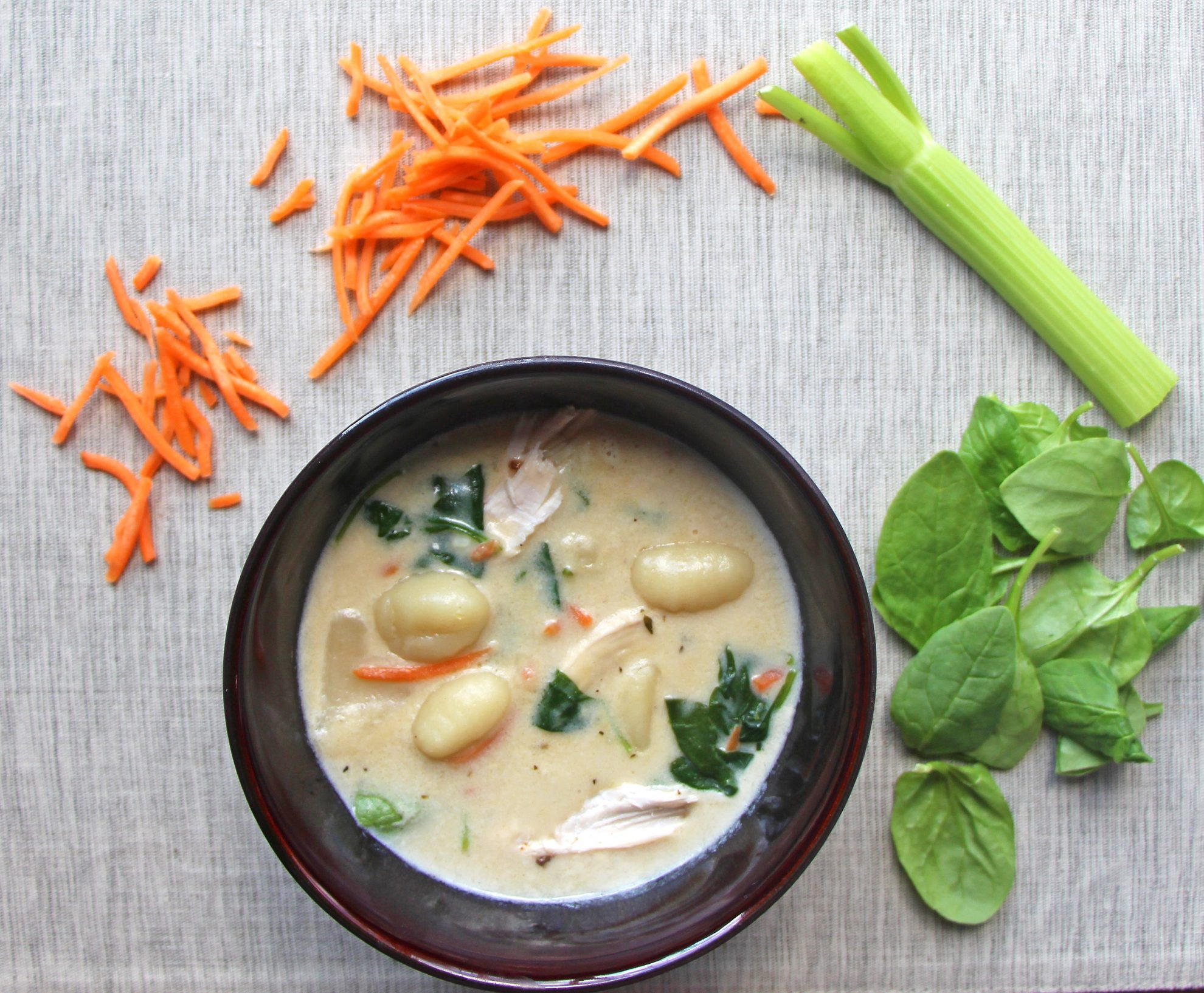 Bowl of dairy-free chicken and gnocchi soup surrounded by carrots, celery, and spinach. this is one of many dairy free chicken recipes on this site.