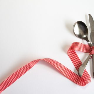 Knife, fork, spoon and ribbon symbolizing addicting AIP snacks, AIP snacks to buy, and best AIP snacks