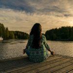 Girl meditating near the water; learn to meditate with this beginner's guide to meditation