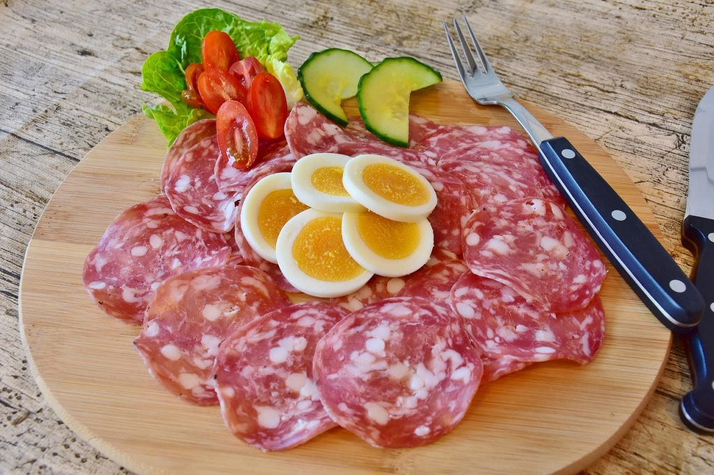 A salumi (charcuterie) plate with salami and egg is a delicious low carb Italian food option when eating out on keto